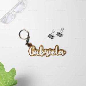 corte láser madera con forma de llavero y la palabra Gabriela con un fondo con gafas y taza de cafè